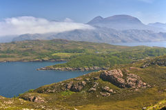 View across the bay towards the mountains, Wester Ross, Schottland. View across the bay towards the mountains with rocky crag in the foreground royalty free stock photos