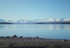 View across a blue lake to snow-capped mountains. A view across a still blue lake to distant snow-capped mountains. The sky is blue, with  no clouds. The shore Stock Photography