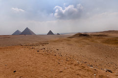 View across the desert to the Pyramids of Giza. View across the desert to the Pyramids of Cheops (Khufu), Khafre (Chephren), Menkaure (Mycerinus) and Queen's Stock Photography