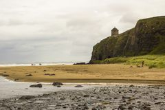 A view across Downhill beach in County Londonderry in Northern Ireland with a train heading toward Mussenden Temple Stock Photos