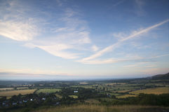 View across English countryside landscape during late Summer eve. English countryside landscape during late Summer afternoon with dramatic sky and lighting Stock Photo