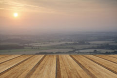 View across English countryside landscape during late Summer eve. English countryside landscape during late Summer afternoon with wooden planks floor Royalty Free Stock Photo