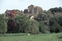 England, Cotswolds, Malmesbury Abbey. View across fields to historic Malmesbury Abbey in early autumn sunshine, Wiltshire, UK Stock Photos