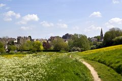 Picturesque Wiltshire, Malmesbury Abbey. View across fields to historic Malmesbury Abbey and the town in spring sunshine in the Cotswolds,Wiltshire, UK Stock Photography