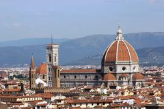 View across Florence, Italy. A view in the sunshine across Florence with the magnificent cathedral in the foreground and mountains as a backdrop against a blue Stock Photo