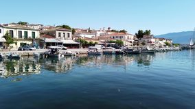 View Across Galaxidi Harbour To Historic Buildings, Greece. View over calm sea water in Galaxidi small harbour to original historic buildings and docked stock footage