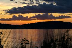 View across the Hudson River, as the sun sets behind the hills and adds a dramatic golden glow to the evening sky. View across the Hudson River as the sun sets stock image
