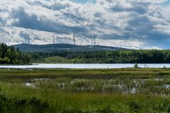 View across a lake in Sweden with bright sky, green forest and some wind power plants in the distance on top of a mountain. View across a lake in Sweden with stock images
