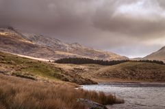 View across the lake to the Snowdon Horseshoe at Llyn Dywarchen, as the sun light breaks over the mountain side in Snowdonia. royalty free stock images