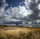 View across Liverpool Bay. Towards Wales from the Sefton Coast with shore and sand dunes and storm clouds Stock Images