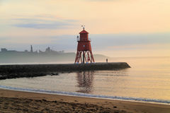 View Across The Mouth of The T. The Red Lighthouse on Legs at the end of the Groyne at South Shields, Tyne & Wear UK. With Tynemouth Priory and the Admiral Lord Royalty Free Stock Photos