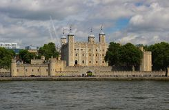 View across the River Thames at The Tower of London. Set on a blue and fluffy cloud sky Royalty Free Stock Images