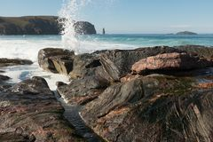 Am Buachaille, Sandwood Bay, Scotland. A view across rocks with water splashing across the sea to the sea stack Am Buachaille and the island of Am Balg Royalty Free Stock Photography