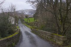 A view across a small stone bridge with a snow topped peak of one of the Mourne Mountains in the background on a dull midwinter af. Ternoon. Taken on a dull Stock Image