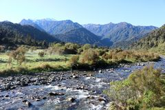 View across stream to mountains, New Zealand. View towards mountains looking across a stream by the side of the Fox Glacier Highway state highway 6 on the West Royalty Free Stock Photos