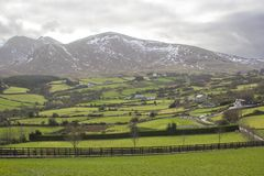 A view across a valley to one of the splendid snow dusted peaks of the Mourne Mountains in County Down Northern Ireland. A view across a valley to one of the Stock Image