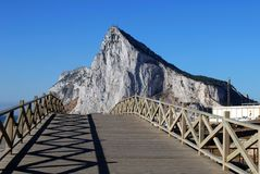 Wooden footbridge and Rock of Gibraltar. Royalty Free Stock Images