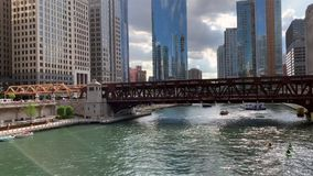 View of activity on the Chicago River including kayaks, water taxi, tour boat, docked recreational boats stock video footage