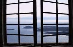 View of the Aegean. View of the Greek island of Paros through a broken window royalty free stock photography