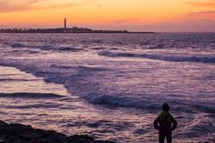 View from afar of the famous lighthouse. And a tourist looking at it - Casablanca - Morocco Stock Photos