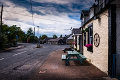 View of Agnew Crescent, Bladnoch, Wigtown, beside Bladnoch Inn Restaurant. With wooden outdoor table and benches for eating and drinking outside royalty free stock photos