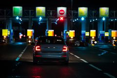 View on an ahead moving car to a checkpoint of multi-lane toll motorway. View on an ahead moving car and a checkpoint of multi-lane toll motorway stock photography
