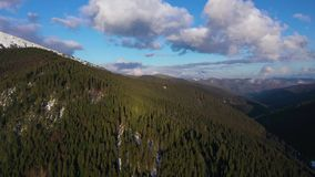 View from the air on clouds on the blue sky over amazing landscape of high snowy mountains and coniferous forest on the stock video
