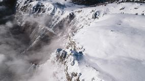 A view from air over the cliffs covered with snow on a sunny day royalty free stock images