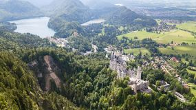 View from the air to the castle of Neuschwanstein castle in the Alpine mountains Royalty Free Stock Images