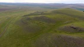A view from the air to the endless fields, hills, haystacks and the sky before the storm in the Republic of Khakassia. Russia stock video footage