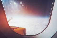 View from aircraft window. Beautiful wide view from window of aircraft: cloudscape, horizon, airplane wing and engine, flare and stylish lens aura Royalty Free Stock Image