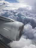 View from aircraft window onto jet engine, wing and cumulus clou Stock Photos