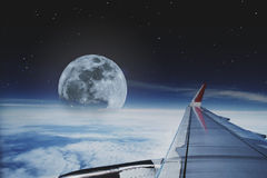 View through aircraft window. traveling by plane with beautiful aerial sky with full moon and stars at night Stock Photo