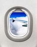 View of aircraft wing and clouds from airplane window Stock Photo