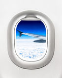 View of aircraft wing and clouds from airplane window Stock Image