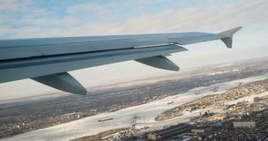 View at aircraft wing from window. Fly over city stock footage