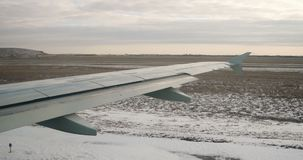 View at aircraft wing from window in winter time, snow on earth. Taxiing airliner stock video