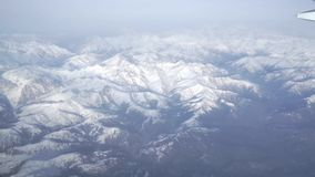 View from airliner porthole with snowy mountains. Clip stock video