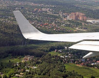 View from airplane. Of the wing and a city beneath Stock Photos