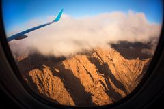 View from an airplane above clouds going home. An image taken from the window of a jetliner. There are clouds and mountains at sunrise Stock Image