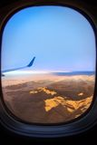 View from an airplane above clouds going home. An image taken from the window of a jetliner. There are clouds and mountains at sunrise Stock Photo