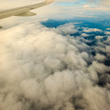 View from airplane flying in clouds. Stock Photos