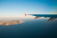 View from the airplane over the sea, the mountains, the wing. Travel Royalty Free Stock Image