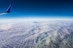 Air travel above the clouds. View from an airplane on a thick cover of clouds above the ocean, with an airplane wing in the corner Stock Photography