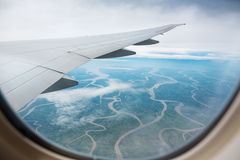 The view from the airplane to the ground dotted with rivers Royalty Free Stock Photo