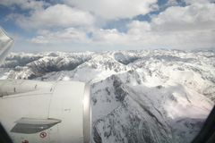 View of airplane turbine engine and snow covered mountains from airplane window. View of airplane engine and snow covered mountains from airplane window. Blue Royalty Free Stock Photography