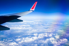 View from airplane window with blue sky and white clouds. Royalty Free Stock Image