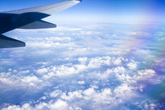View from airplane window with blue sky and white clouds. Stock Image