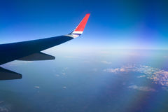View from airplane window with blue sky and white clouds. Stock Photos