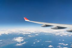 View from airplane window with blue sky and white clouds.  Stock Photography